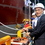 (Mr. Takaaki Anraku, President Kokusai Cable Ship Company Ltd of Japan, cutting the rope to break the milk pot against the vessel's hull)