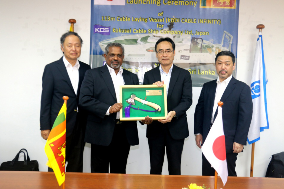 """Mr. D.V. Abeysinghe MD/CEO Colombo Dockyard PLC presenting the symbolic axe used to launch the Cable Laying Vessel """"KDDI CABLE INFINITY"""", flanked by Dr. Toru Takehara Chairman CDPLC and Mr. Yukihiro Fujii Managing Director KCS"""